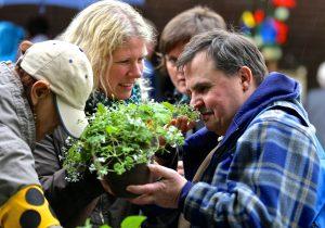 Gruppe von Menschen riecht an einer Pflanze