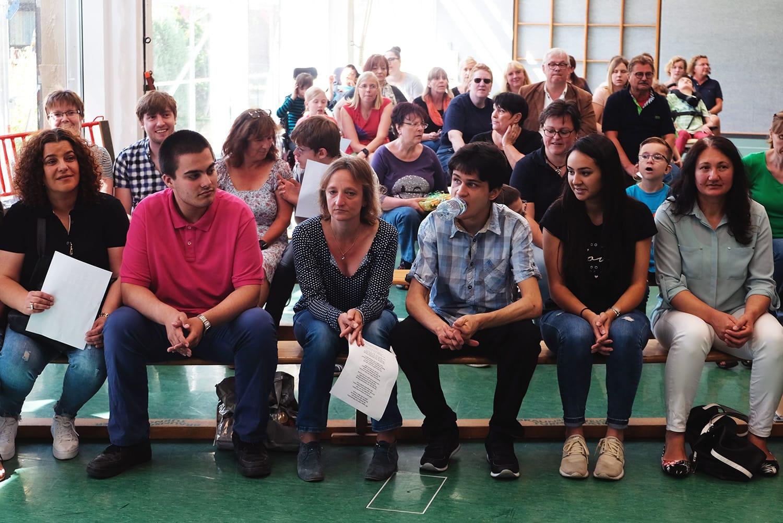 Schüler, Lehrer, Erzieher und Eltern sitzen auf Bänken