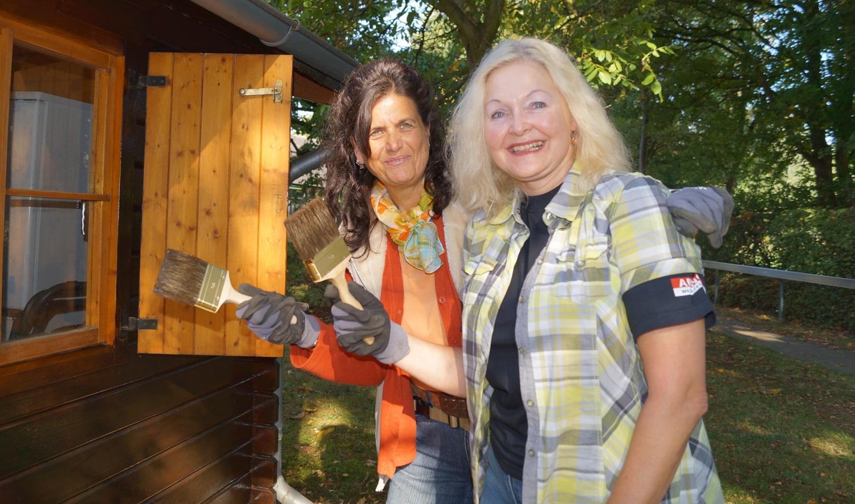 zwei Frauen stehen mit Pinseln und Handschuhen neben einer frisch gestrichenen Holzhütte