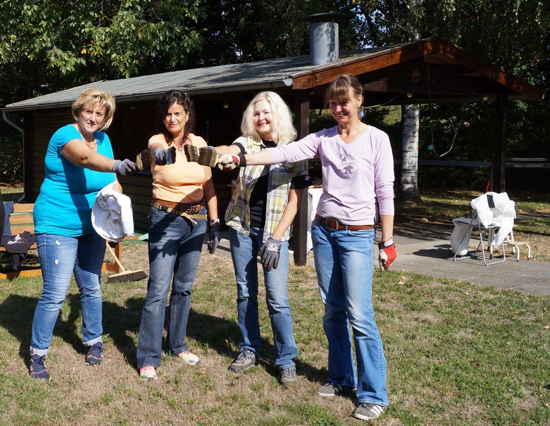 vier Frauen mit Pinsel in der Hand freuen sich über die fertig gestrichene Holzhütte