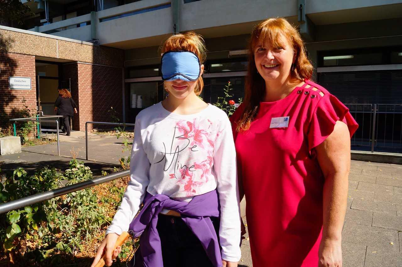 Reha-Lehrerin Regina Berg hilft Angelina, sich mit Blindenstock und Augenbinde zu orientieren