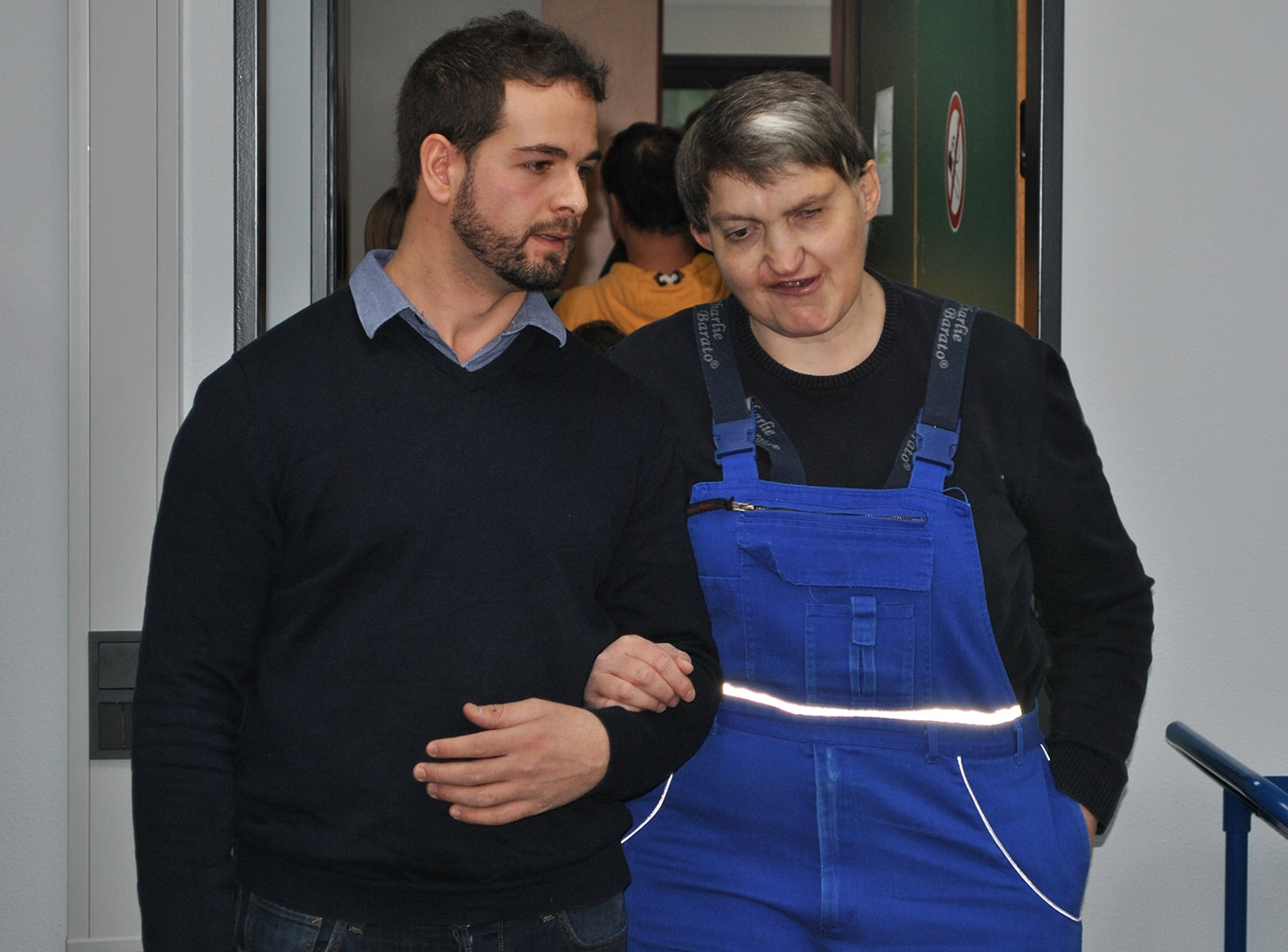 Mann begleitet Beschäftigten an seinen Arbeitsplatz