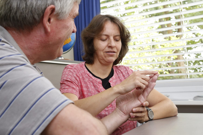Beraterin spricht mit taubblindem Klienten