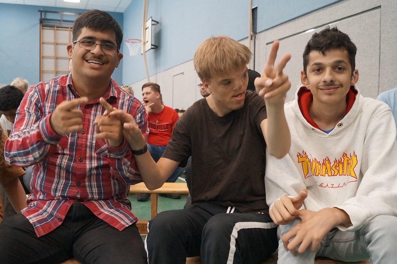 Ferhat (links) und Jack (rechts) sitzen neben ihrem Mitschüler und Freund Lucas