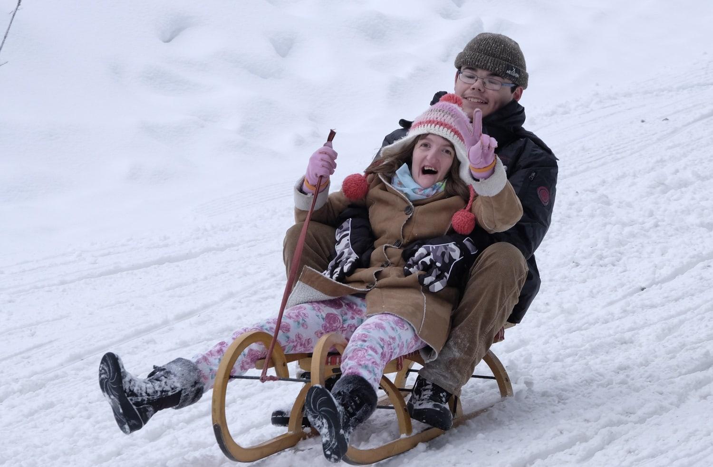Mädchen und Junge sitzen auf einem Schlitten und rodeln