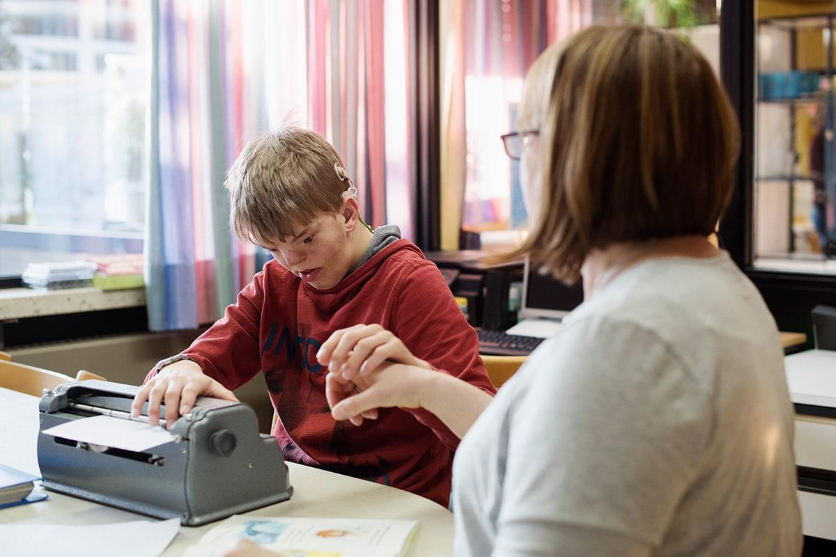 Lukas lernt an der Punktschriftmaschine zu schreiben
