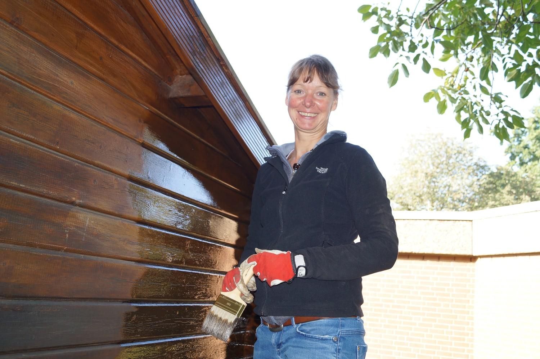 Frau mit Pinsel und Handschuhen steht lachend neben einer Holzhütte