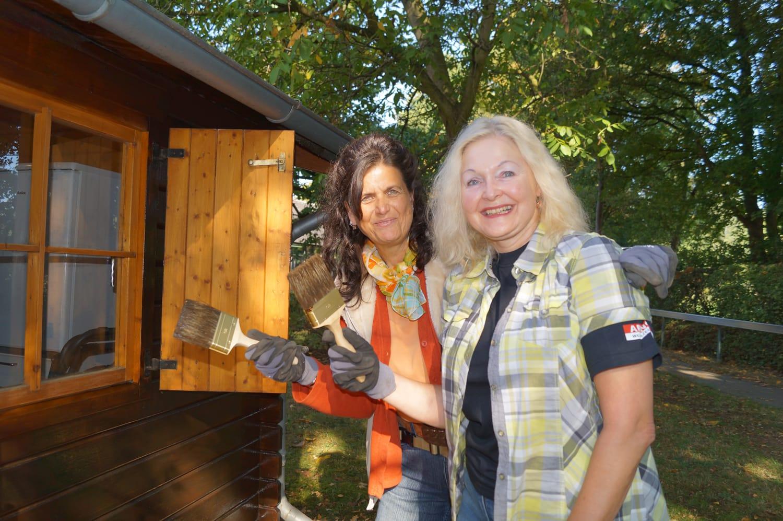 zwei Frauen stehen mit Pinsel und Handschuhen neben einer frisch gestrichenen Holzhütte