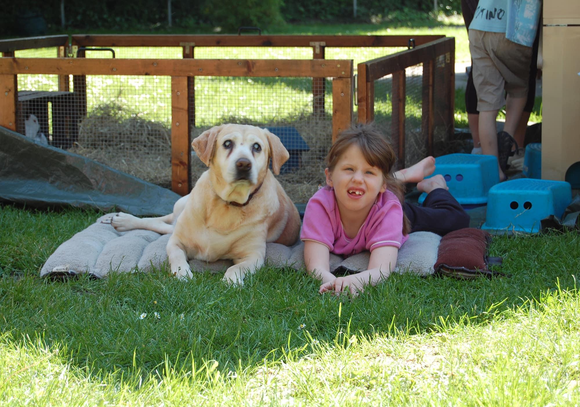 Mädchen liegt neben einem Hund auf der Wiese