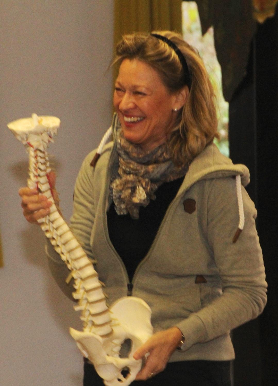 Frau mit Skelett der Wirbelsäule in der Hand