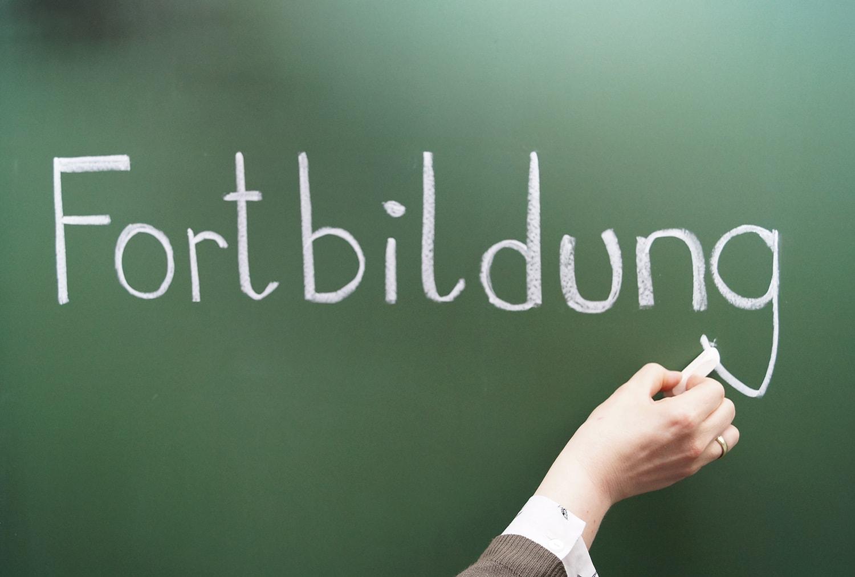 Frau schreibt mit Kreide das Wort Fortbildung an eine Tafel