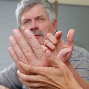 Frau kommuniziert mit taubblindem Mann über die Hand