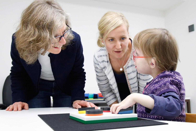 zwei Lehrerin sprechen mit einem Mädchen
