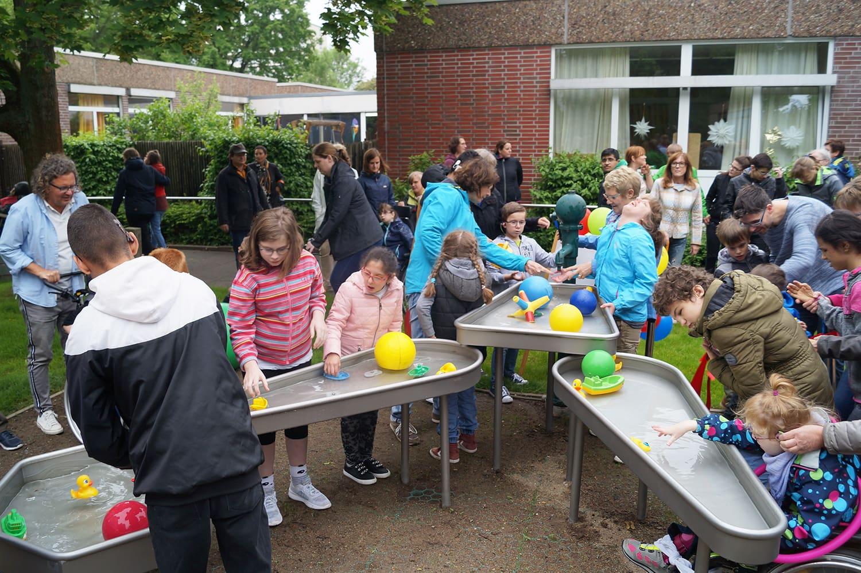 viele Schüler planschen und haben Spaß mit dem Wasserspielplatz