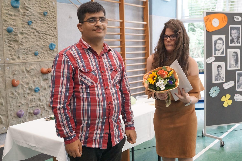 Ferhat steht neben Krenare, die einen Blumenstrauß in der Hand hält