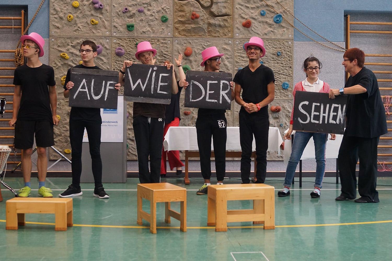 Schüler halten Schilder in den Händen, auf denen Auf Wiedersehen steht