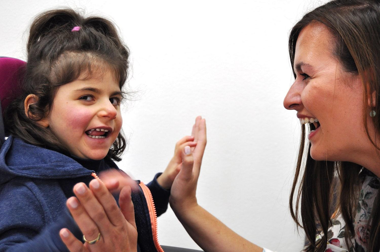 Lehrerin spielt mit einem fröhlichen Mädchen