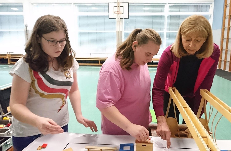 Maria und Ayla bewegen Figuren über das Modell der Turnhalle