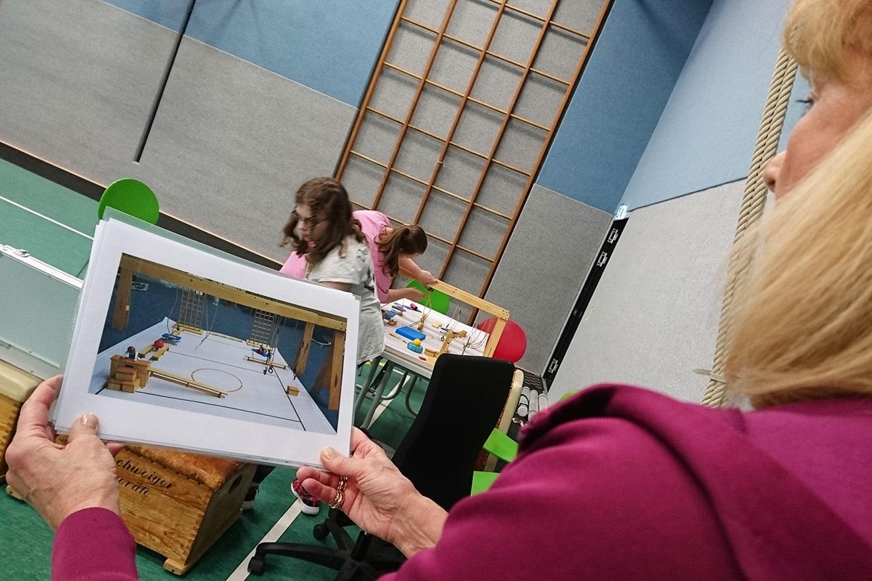 Sportlehrerin zeigt ein Foto von einer Sportstunde, wie sie sich Schüler wünschen