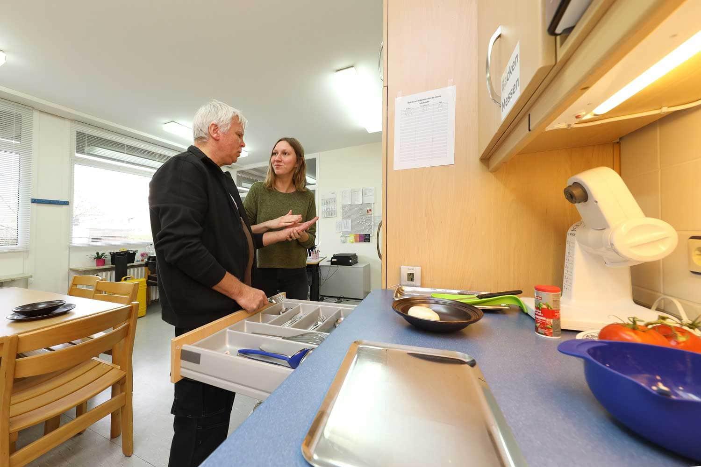 Franz Pirker steht neben seiner Betreuerin in der Küche
