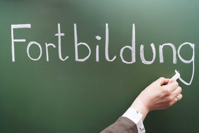 Frau schreibt mit Kreide das Wort Fotbildung an eine Tafel