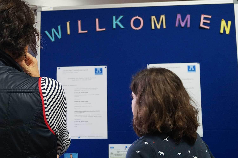 Besucher stehen vor einer Informationstafel