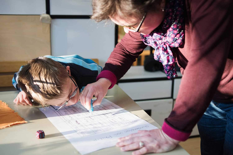 Junge beugt sich über einen Zettel und daneben steht seine Lehrerin