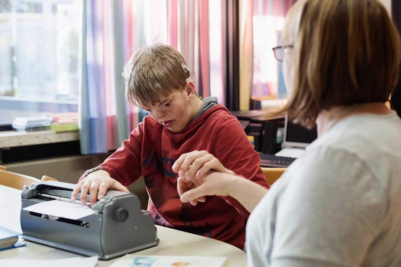 Junge lernt Braille an einer Schreibmaschine