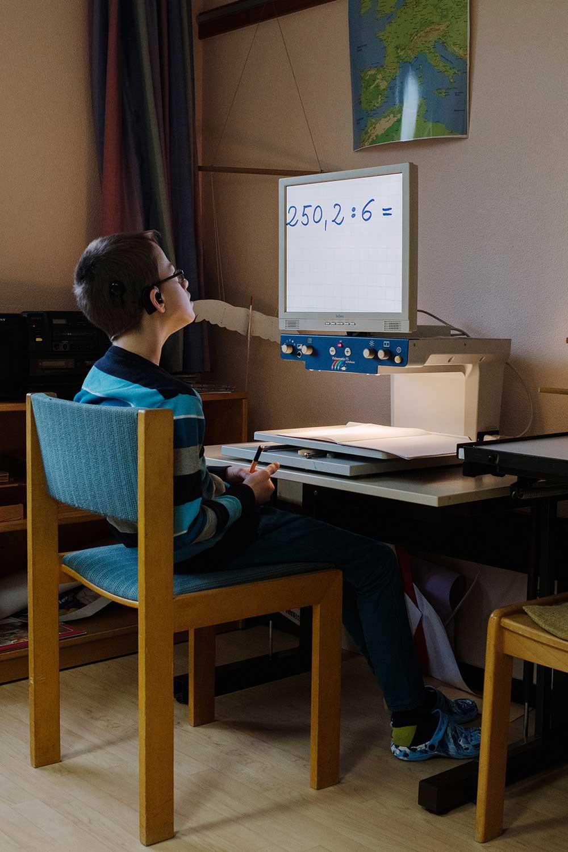 Junge sitzt vor einem Bildschirm und löst eine Rechenaufgabe