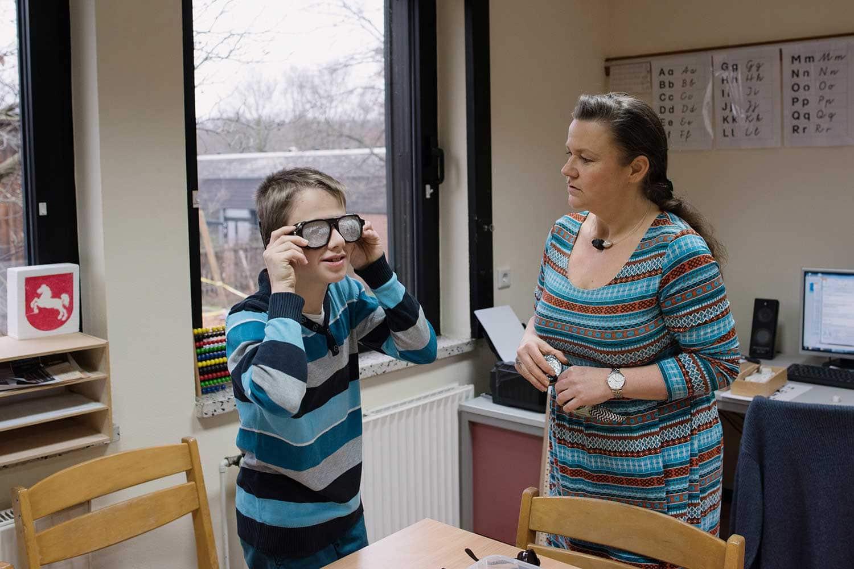 Junge probiert mit seiner Lehrerin eine Brille
