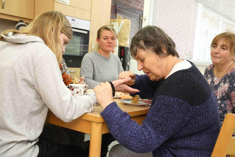 Menschen sitzen zusammen an einem Tisch und sprechen miteinander