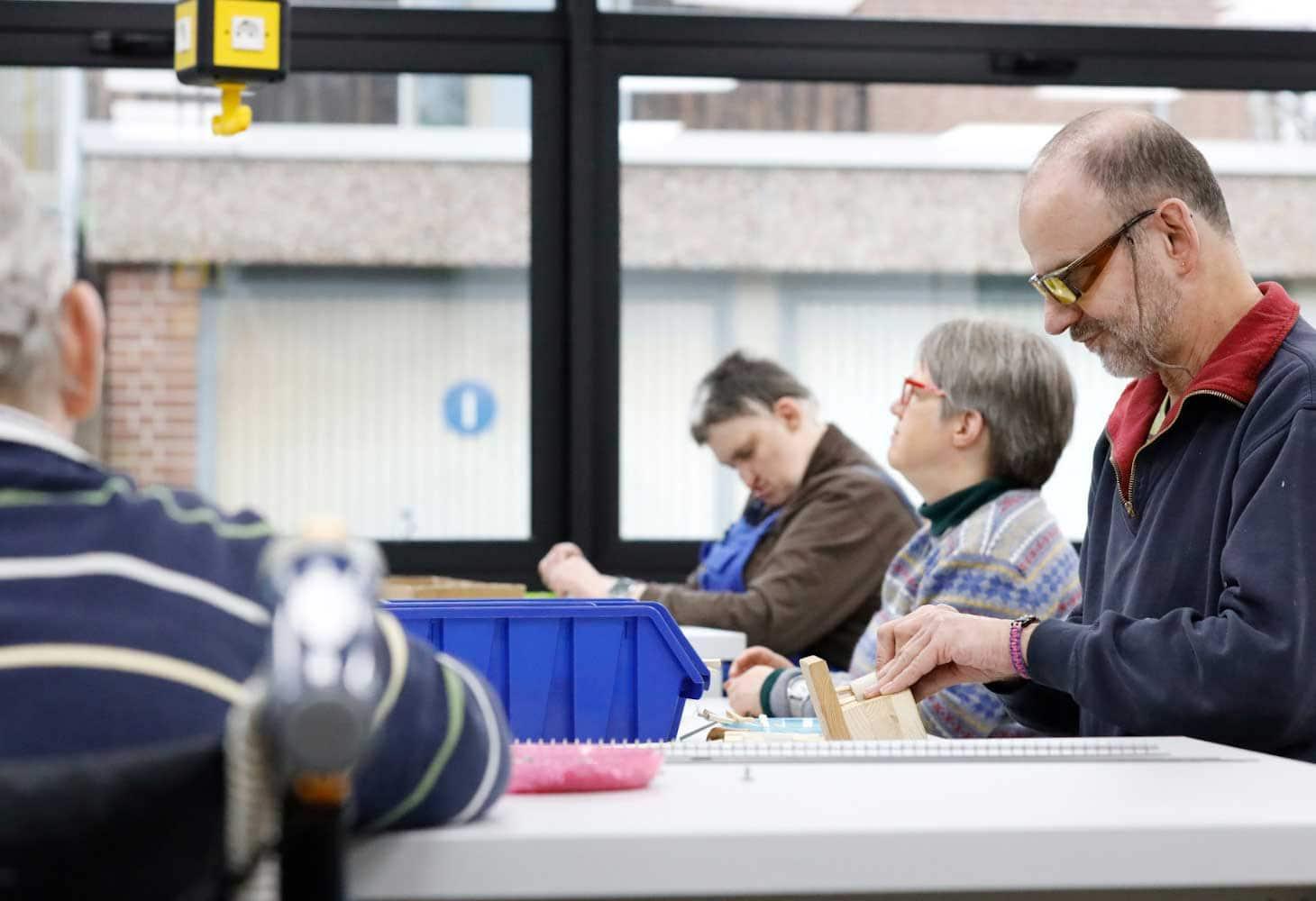 Taubblinde und hörsehbehinderte Menschen sitzen an einem Tisch und arbeiten
