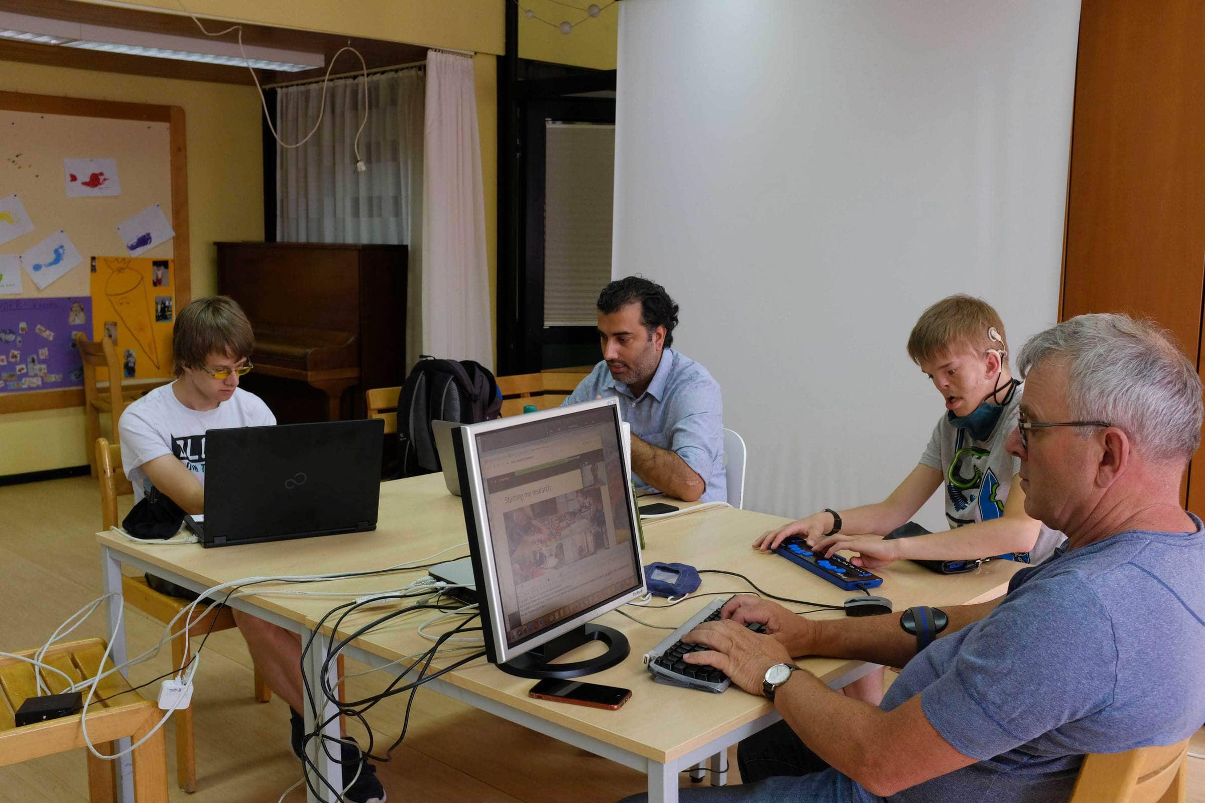 Schüler und Lehrer sitzen am Tisch und arbeiten an Rechnern