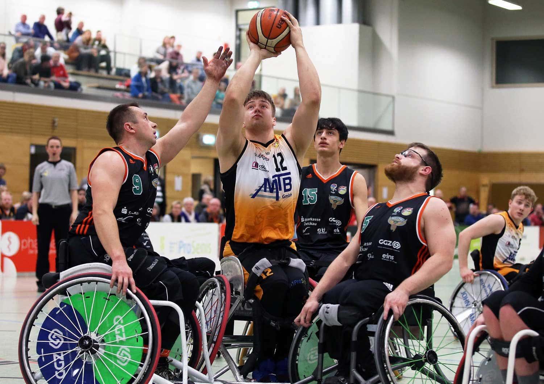Rollstuhlbasketballer wirft einen Ball in den Korb