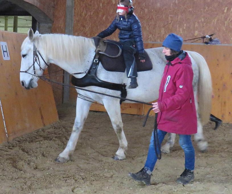 Schüler hat die Augen verbunden und reitet auf einem Pferd