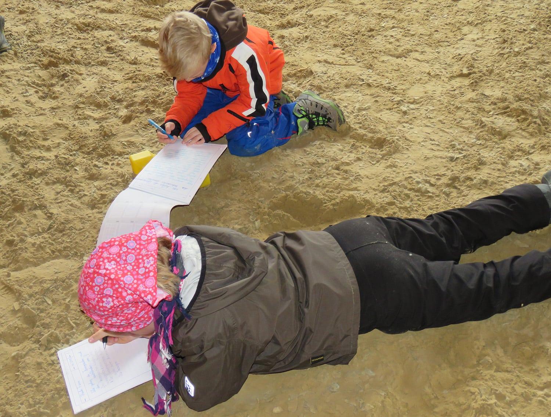 Kinder liegen im Stroh und machen sich Notizen