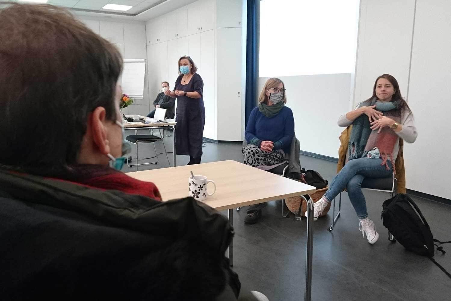 Gebärdensprachdolmetscherin übersetzt den Vortrag für einen Teilnehmer