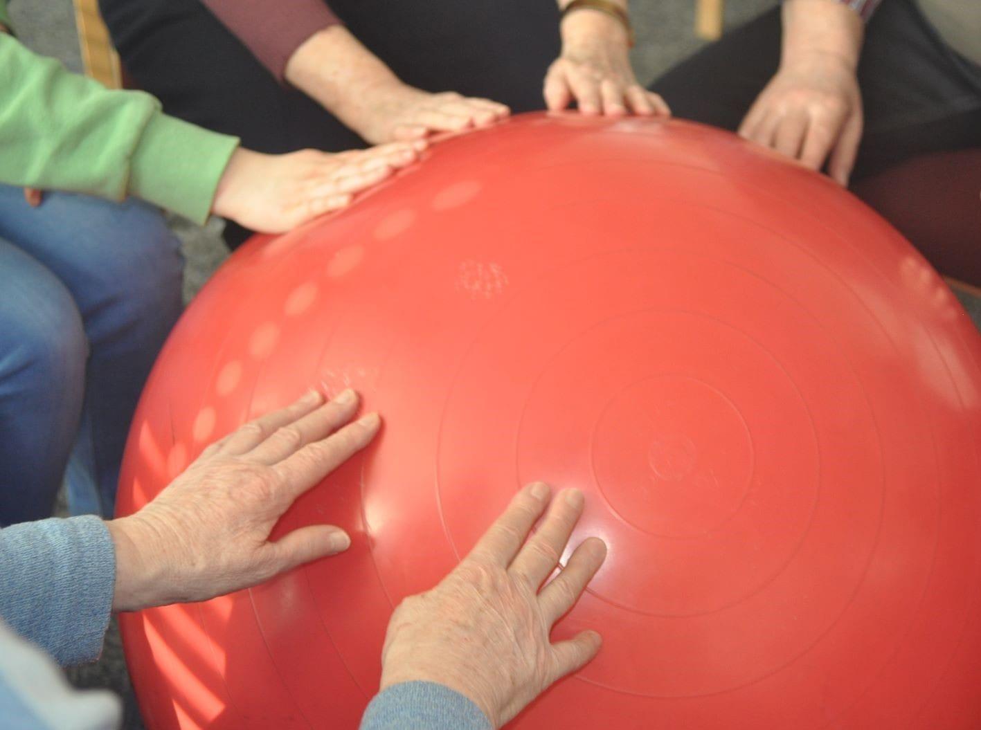 Viele Hände liegen auf einem Ball