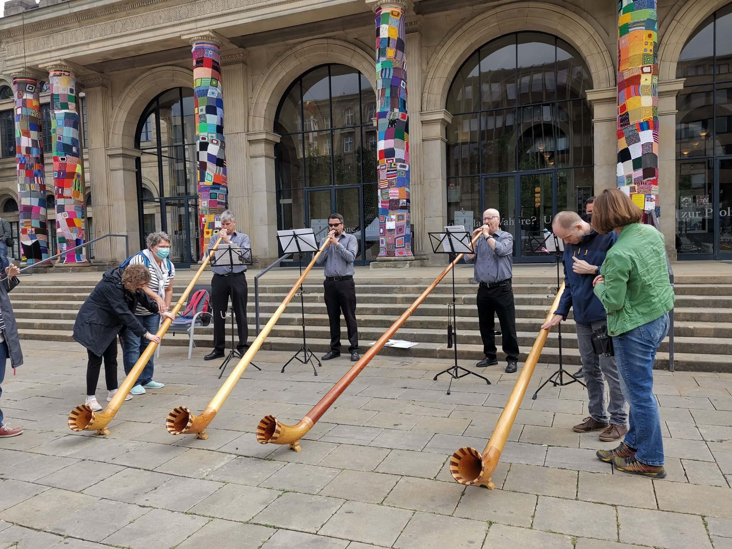 Alphornbläser spielen, Menschen mit Taubblindheit befühlen die Instrumente