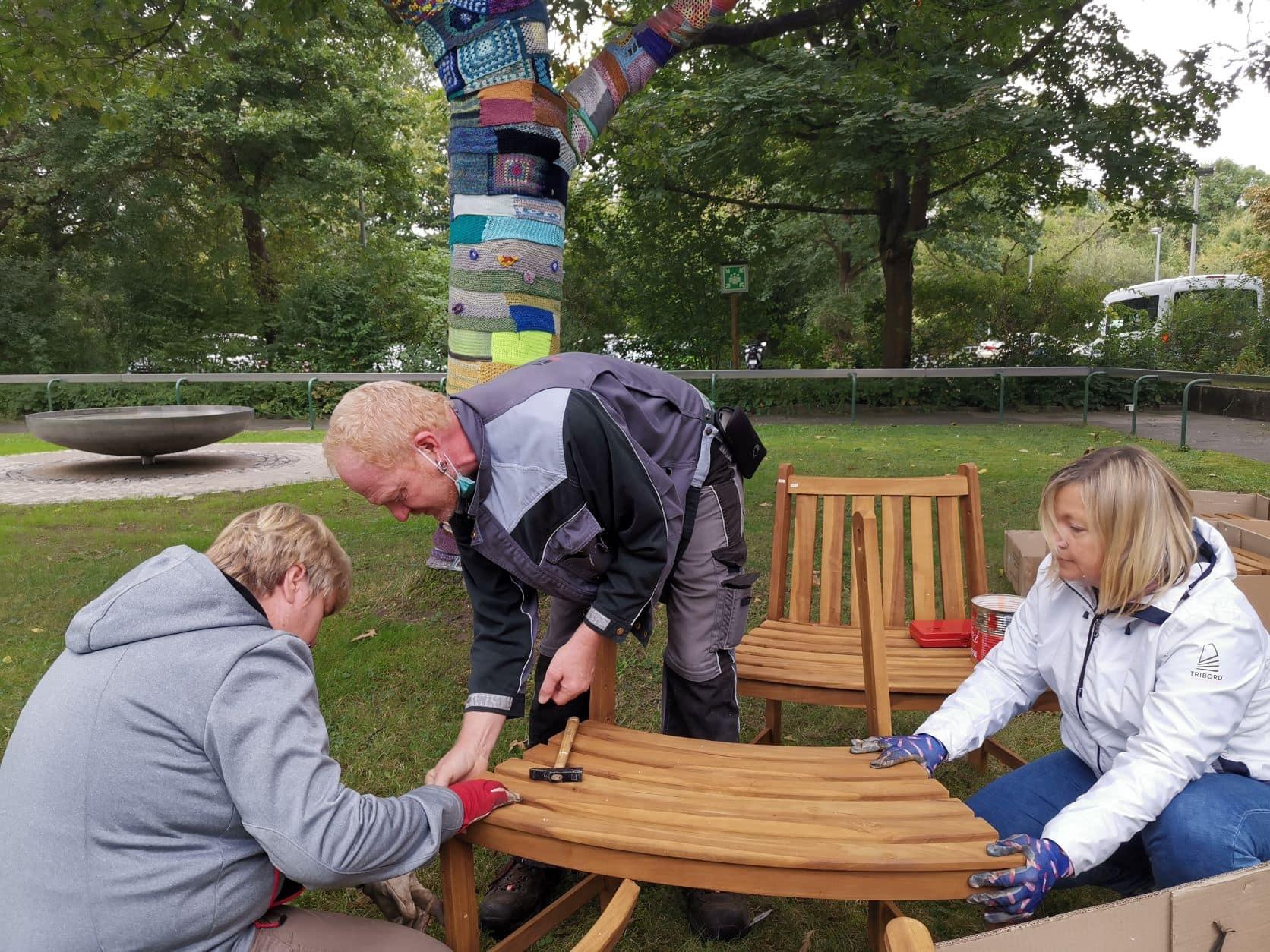 Drei Personen bauen eine Rundbank auf