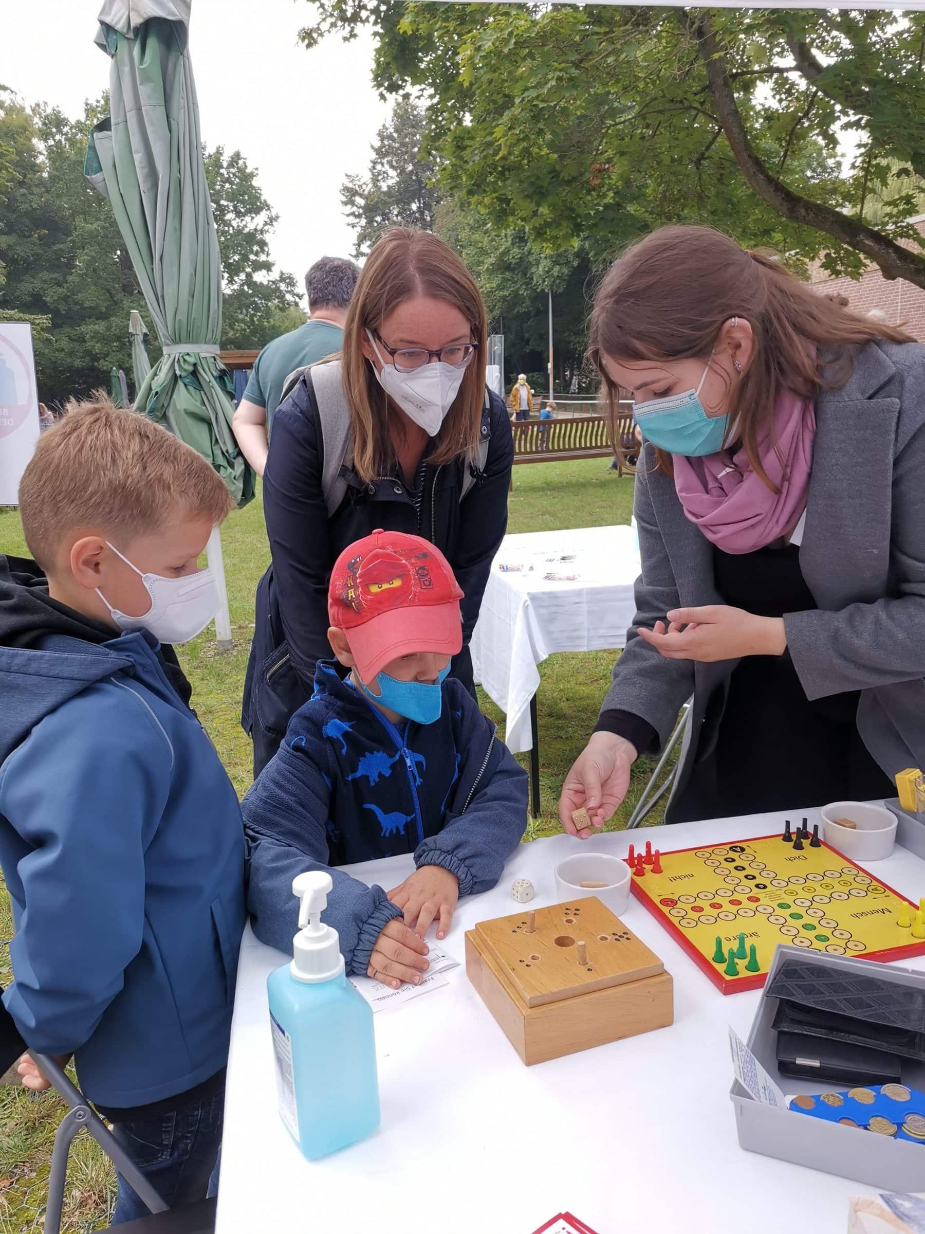 Eine Frau und zwei Jungen beugen sich interessiert über ein Brettspiel für taubblinde Menschen