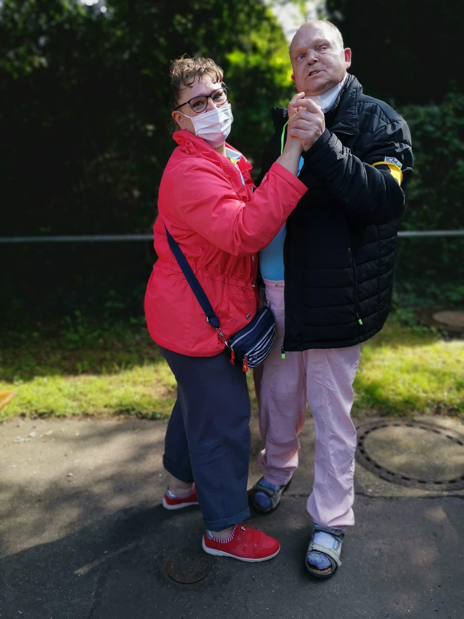 Eine Frau und ein Mann mit Sehbehinderung tanzen draußen