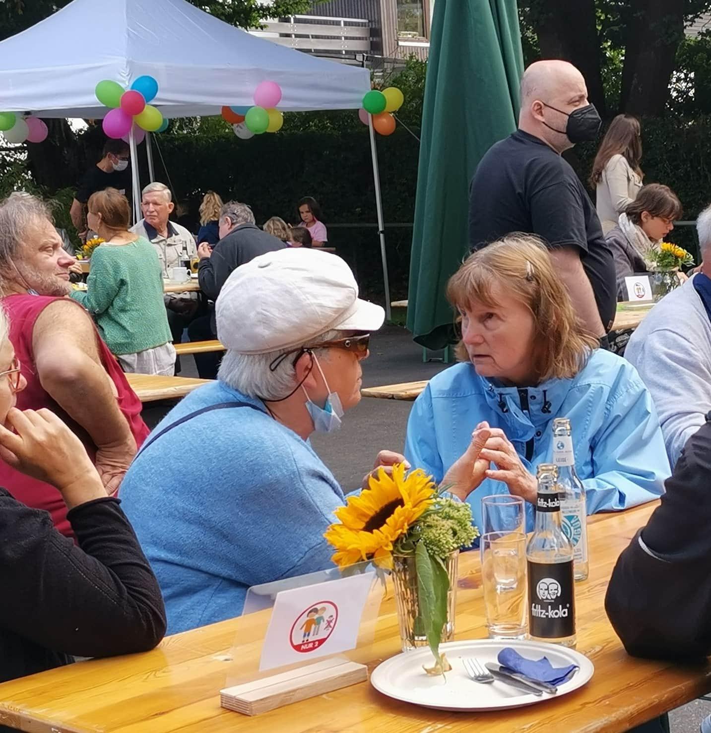 Gäste sitzen draußen am Tisch, zwei Frauen lormen