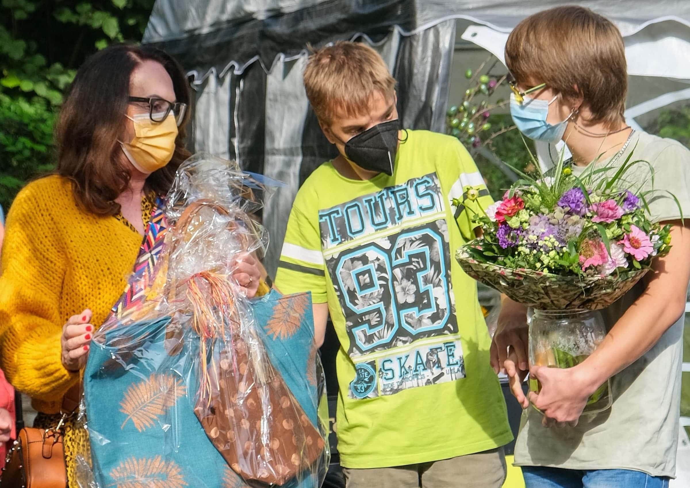 Ehemalige Mitarbeiterin wird von zwei Jugendlichen mit Hörsehbehinderung verabschiedet
